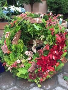 Kranz mit herbstlichem Grün und roten Nelken